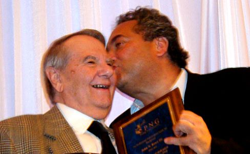 PNG member Kevin Lipton (right) playfully kisses John N. Rowe III after giving Rowe a plaque marking his 50 years as a PNG member-dealer.     Photo by Donn Pearlman.  All rights reserved.