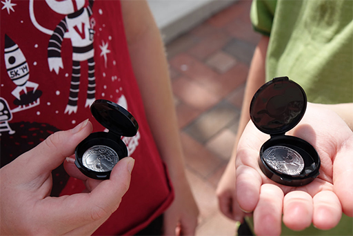 A pair of children examine their new coins.