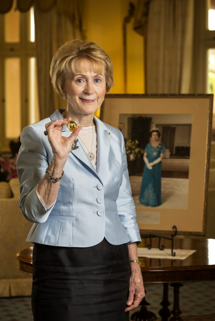 Her Excellency the Honourable Kerry Sanderson AO, Governor of Western Australia pictured in Government House holding the H.M. Queen Elizabeth II 90th Birthday 2oz Gold Proof High Relief Coin, in front of a portrait of Her Majesty.